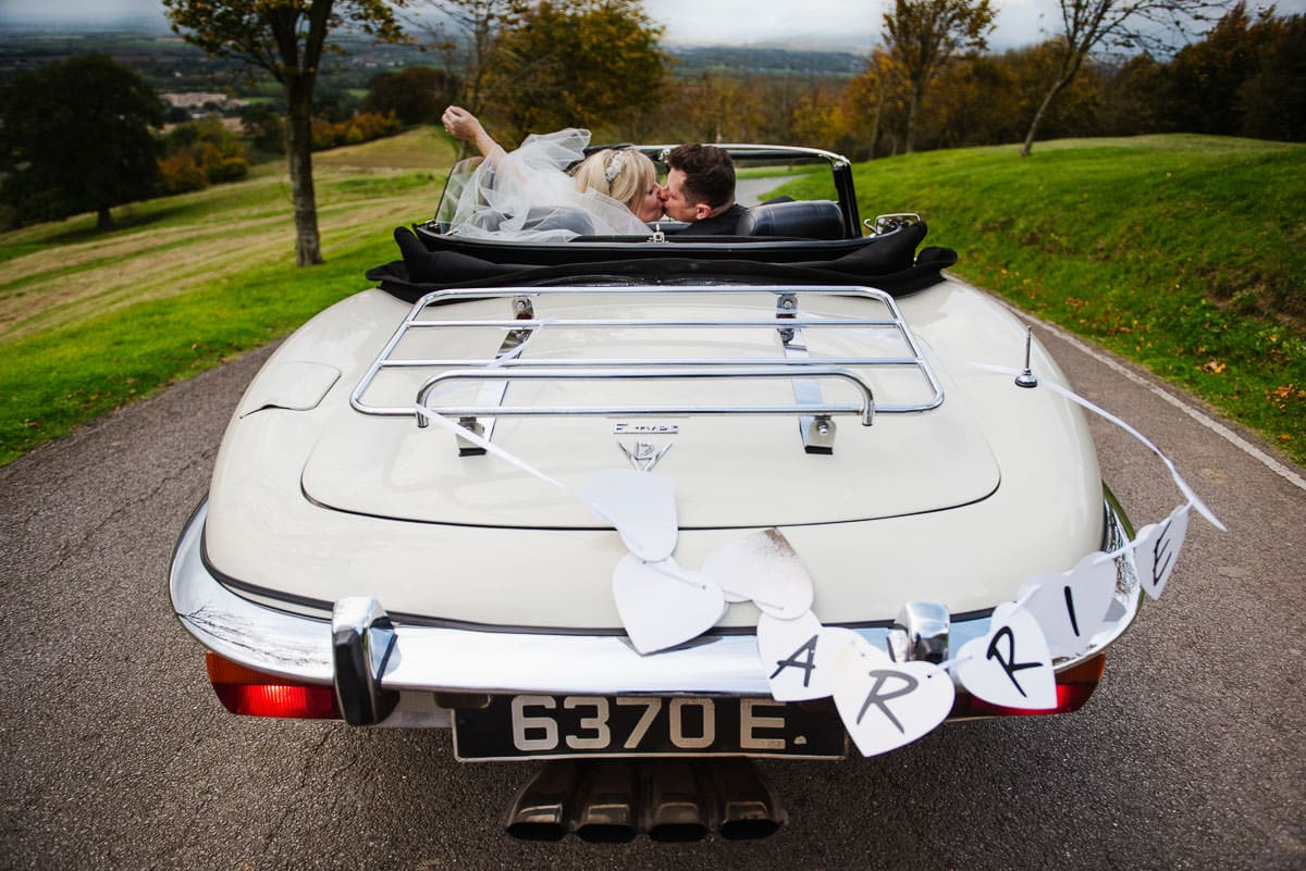 bride and groom kiss in Jaguar E-type motor car