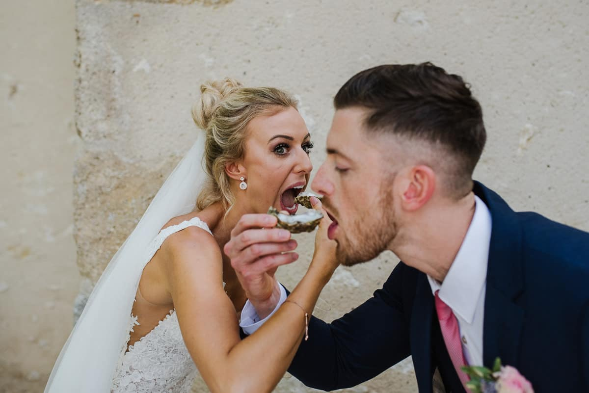 Bride and groom eating oysters
