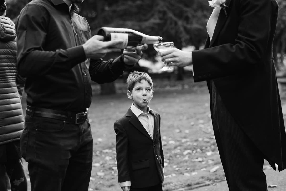 Young child watches as champagne is poured at wedding