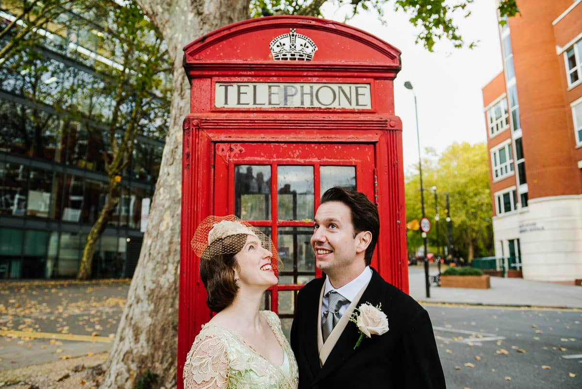 Bride and Groom in 1920s wedding fashion by London red telephone box