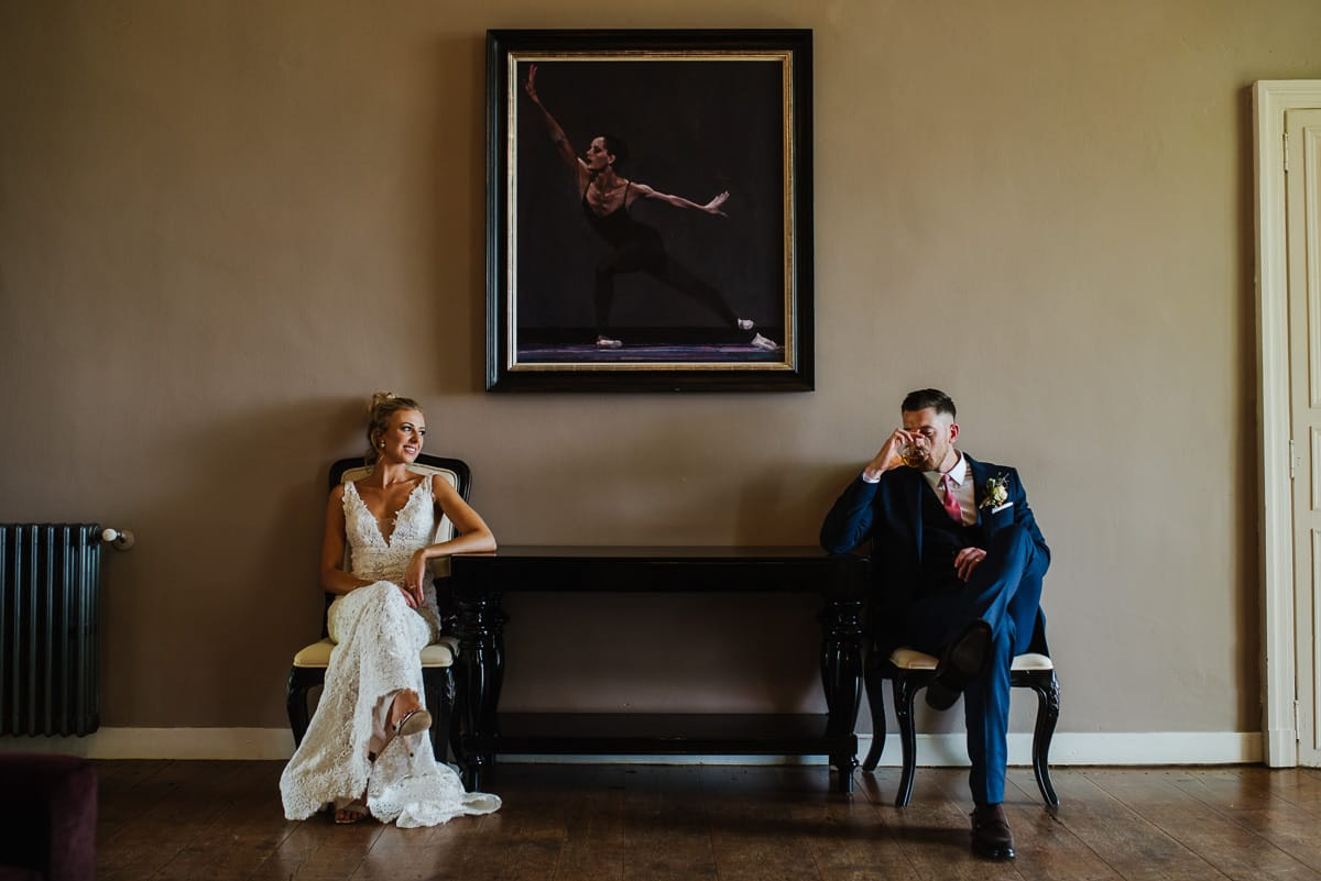 Stylish bride and groom with painting of dancer Darcy Bussell