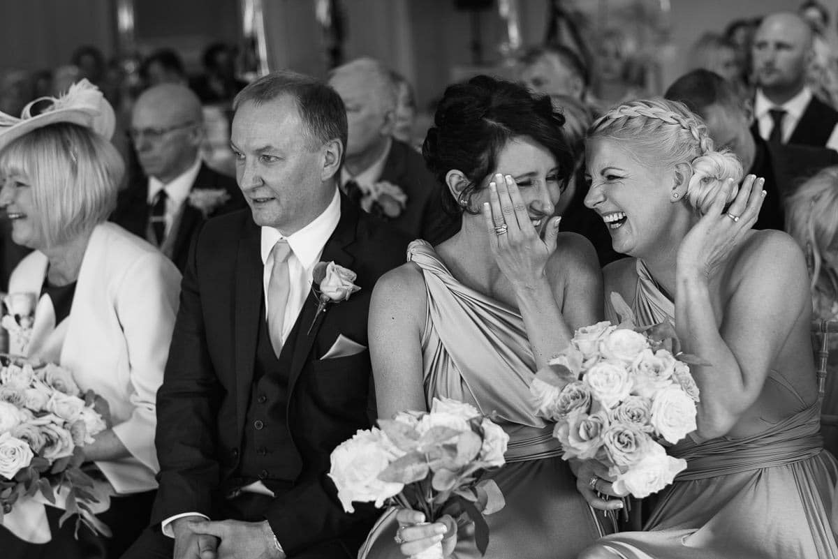 bridesmaids share a joke during the wedding ceremony