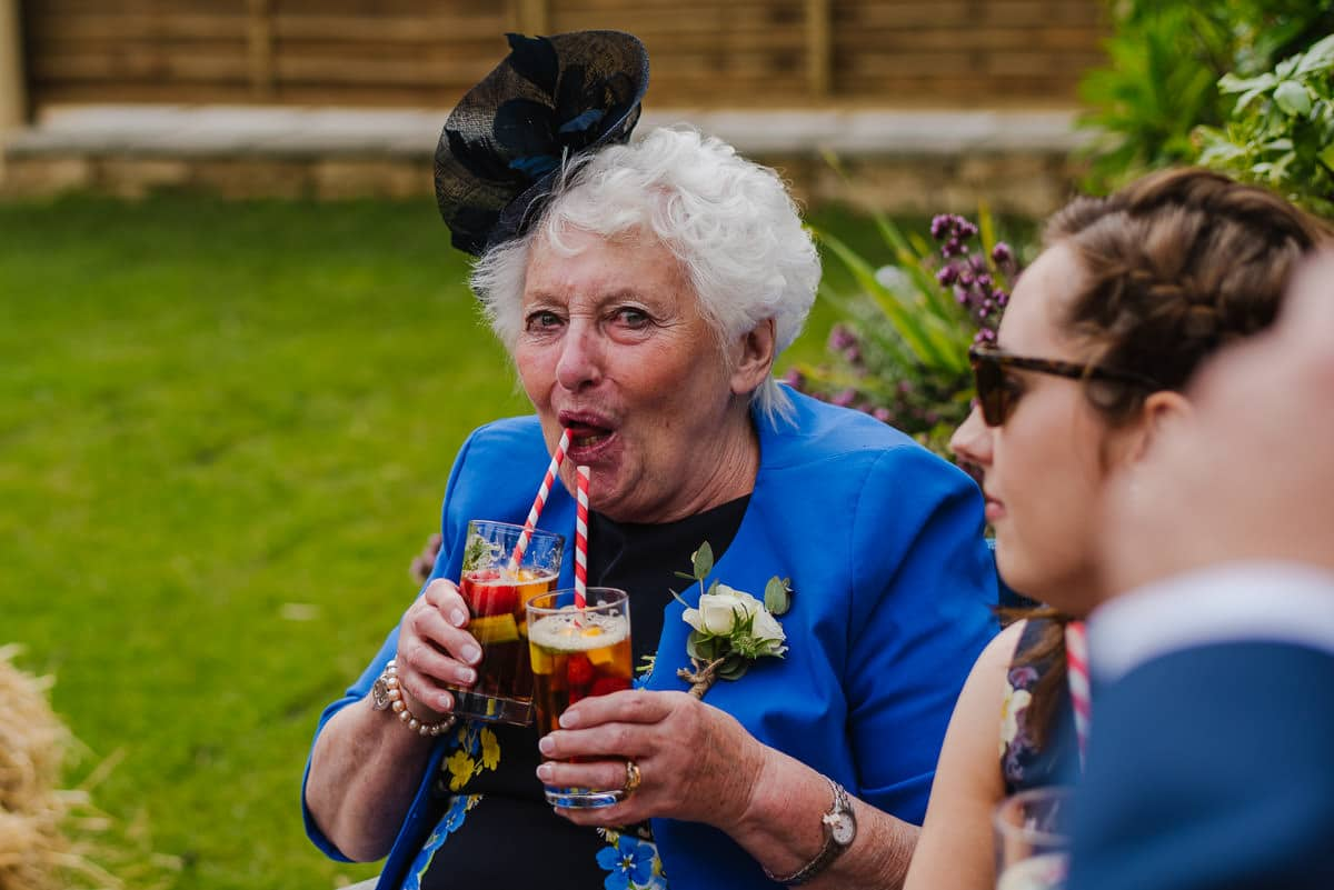 Wedding guest drinking two english pimms cocktails