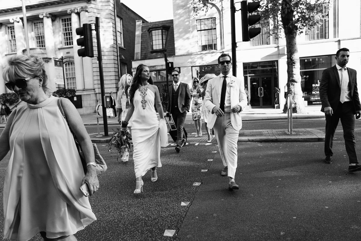 Classic black and white image of bride and groom crossing the road