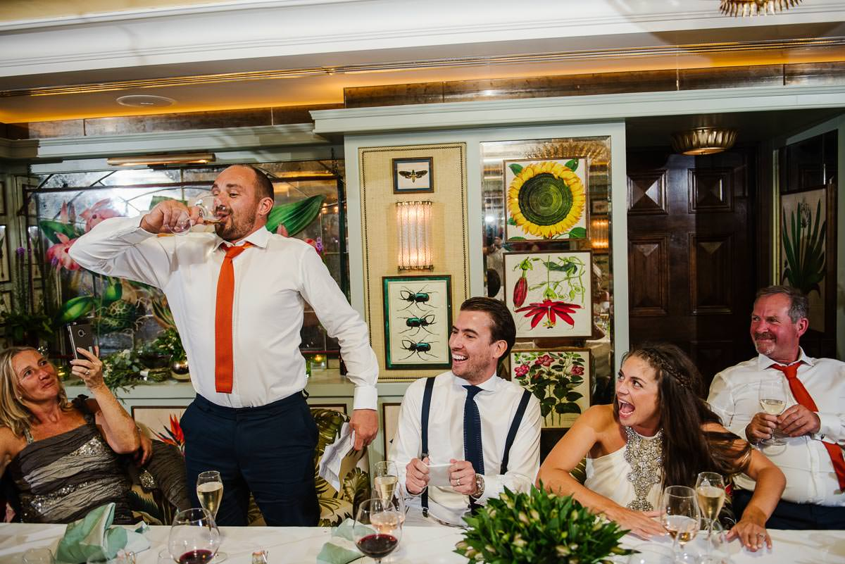 best man downs a drink at the top table before his speech