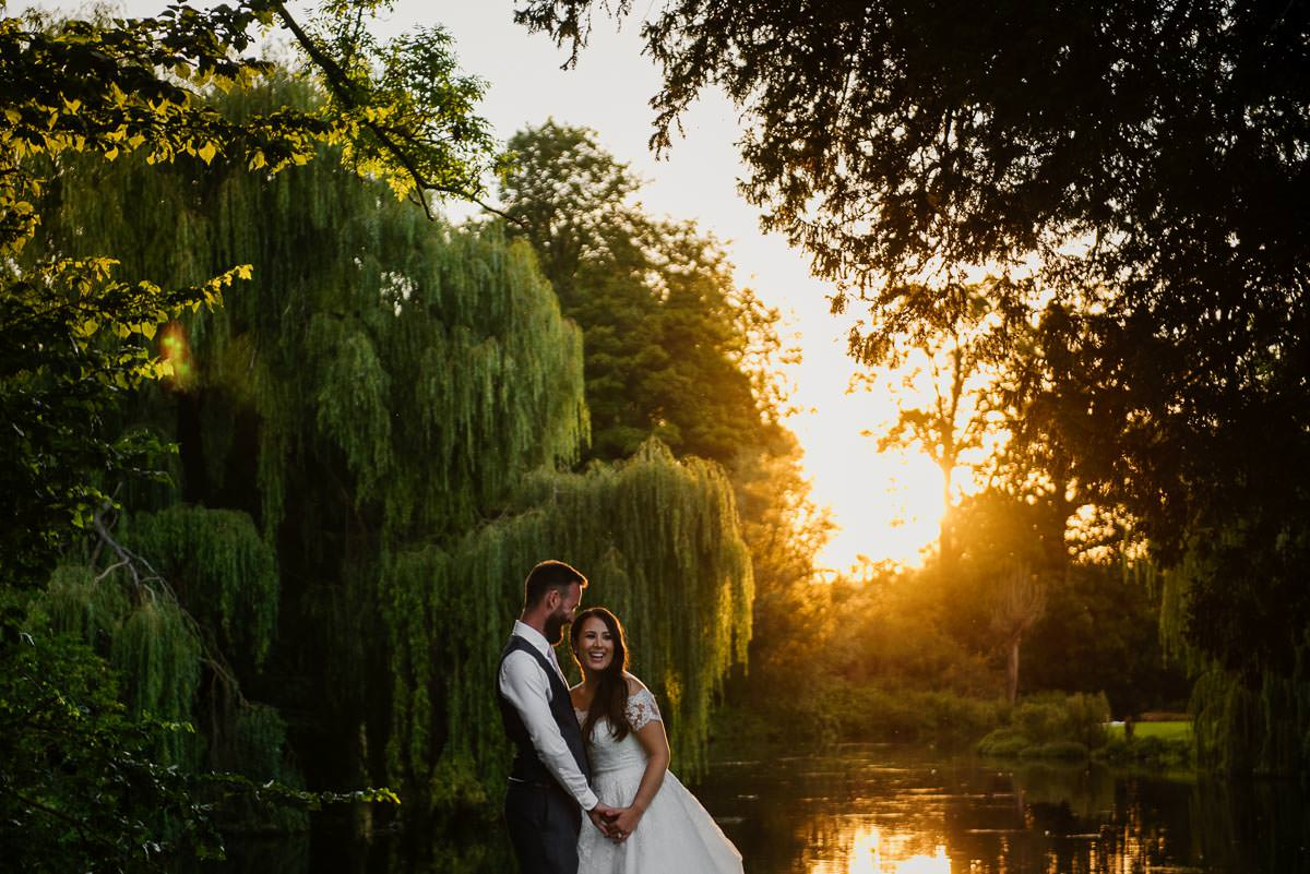 Bride and groom watching beautiful golden sunset