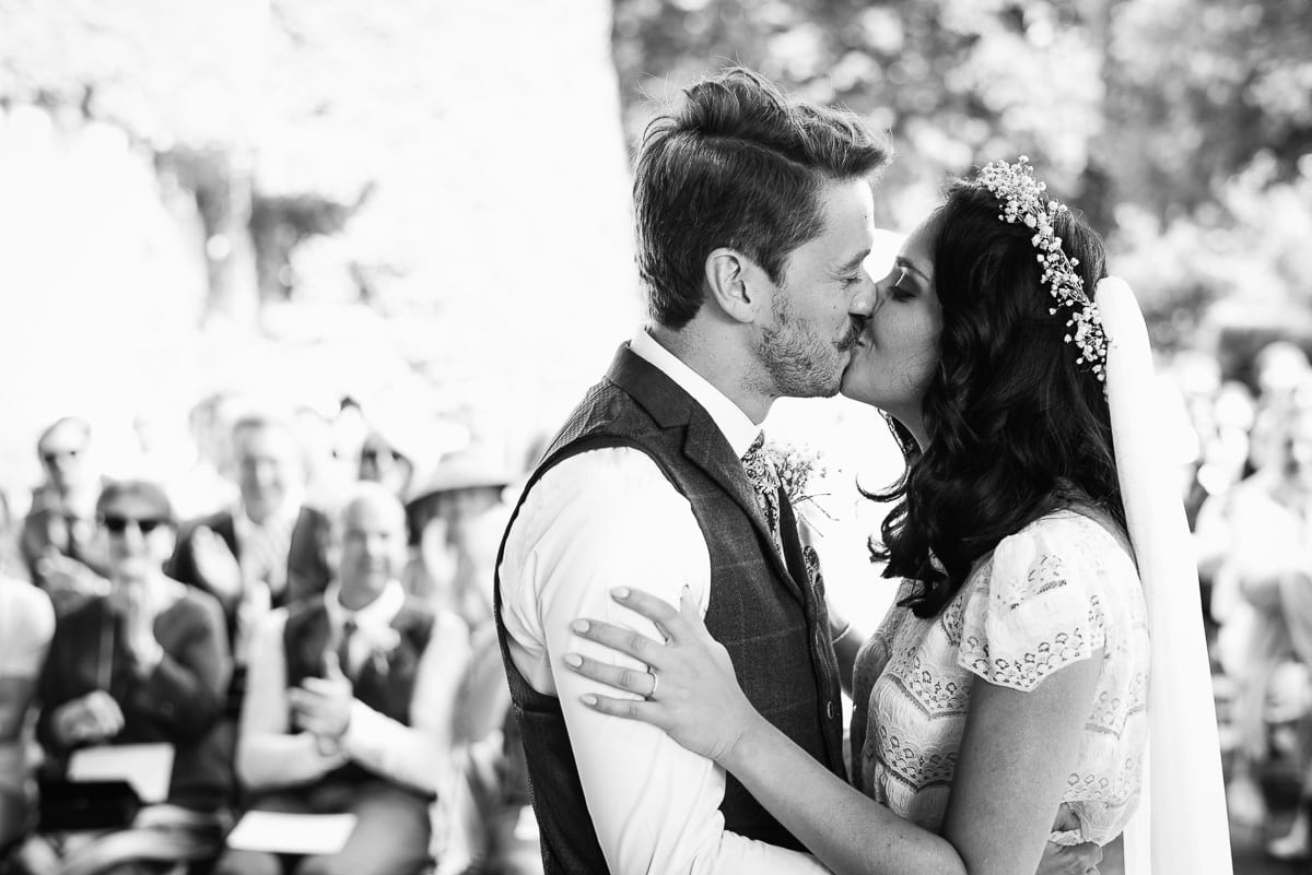 Classic black and white image of bride and groom's first kiss