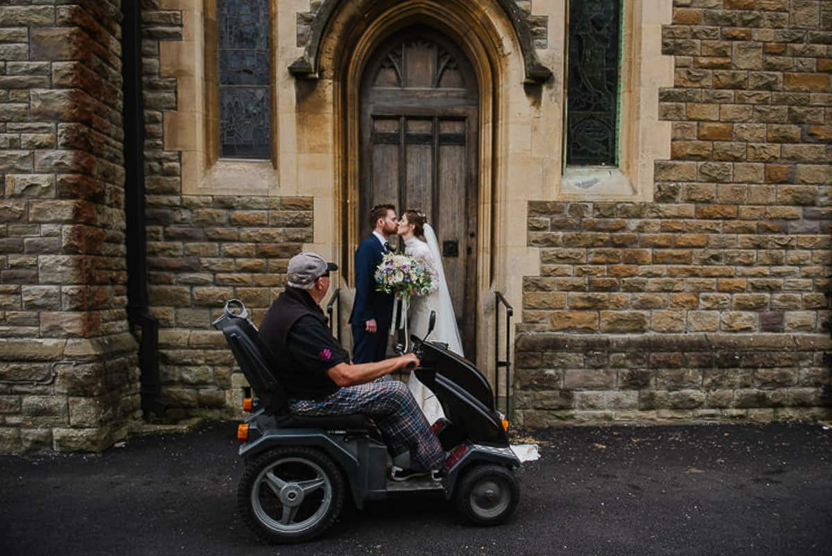 man on mobility scooter interrupts bride and groom kissing