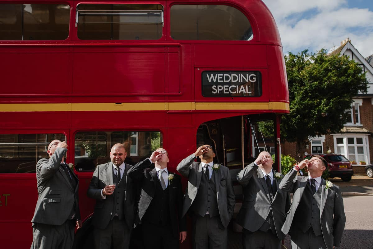 Groomsmen drinking shots by London double decker bus