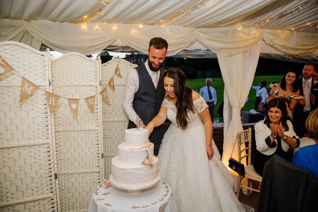 Cutting the wedding cake bride and groom marquee ardington house