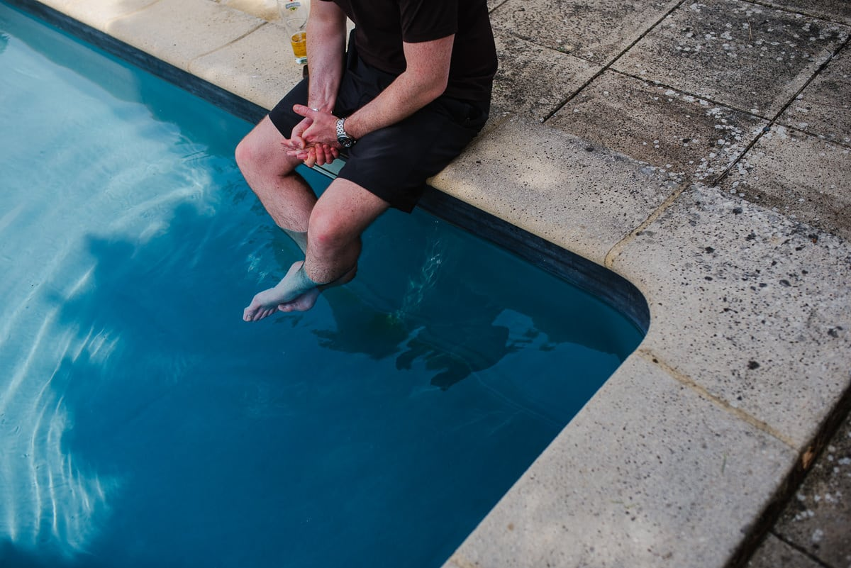 Guest with feet in swimming pool at Chateau les merles France