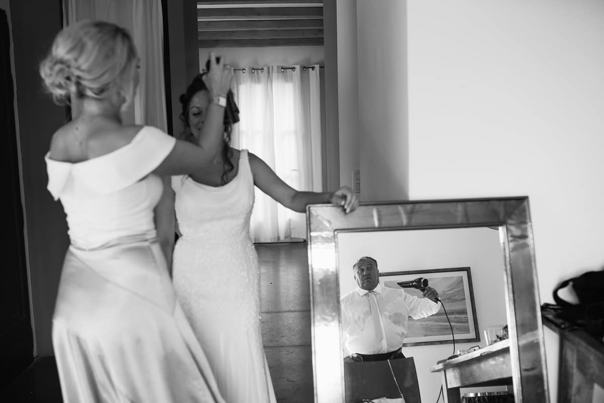 documentary photo of bride getting ready assisted by bridesmaid