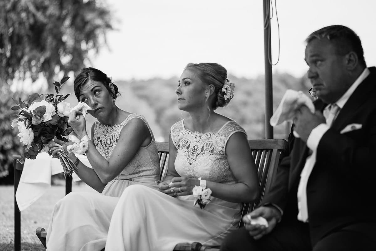 Bridesmaid wiping away tears during ceremony