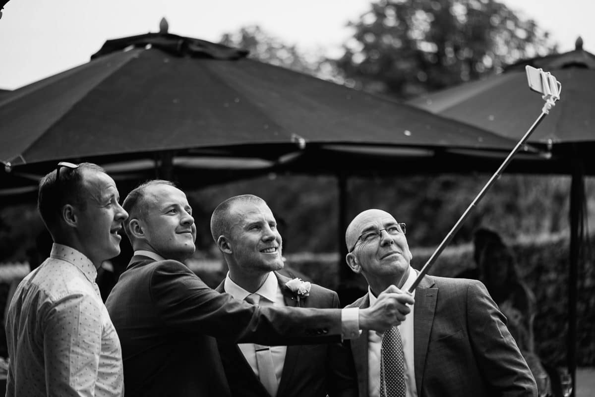 Guests in wedding suits taking selfie with a selfie stick