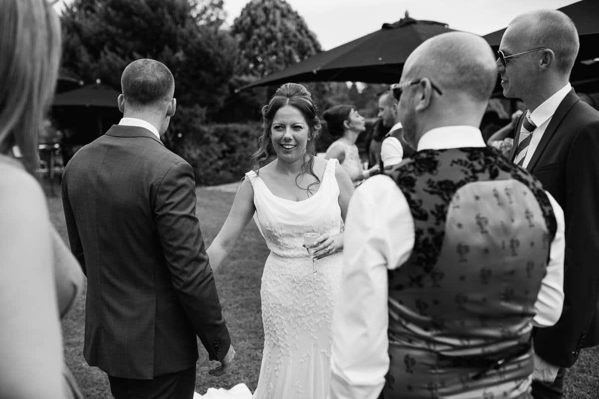 bride in wedding dress with guests having a laugh