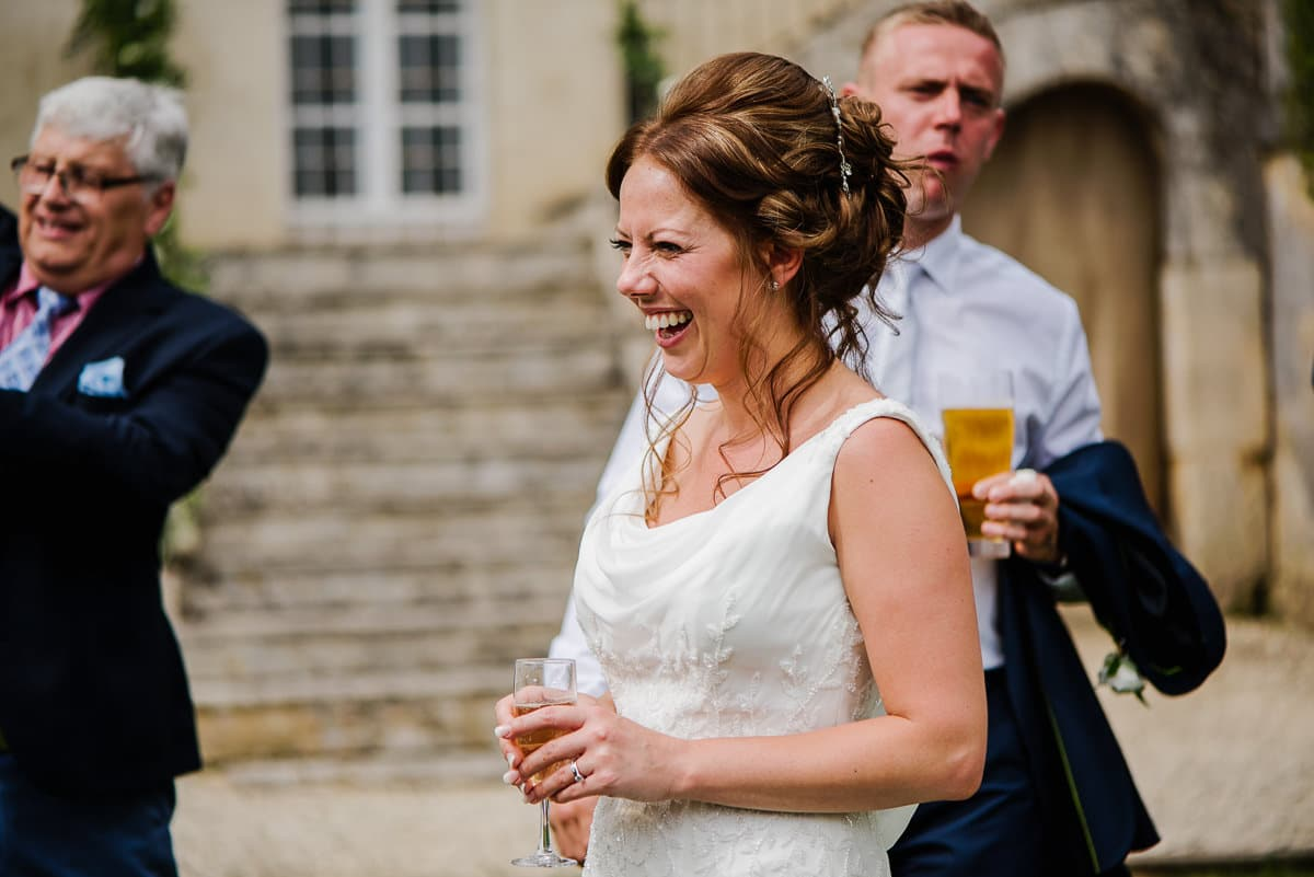 Bride laughing with a glass of champagne