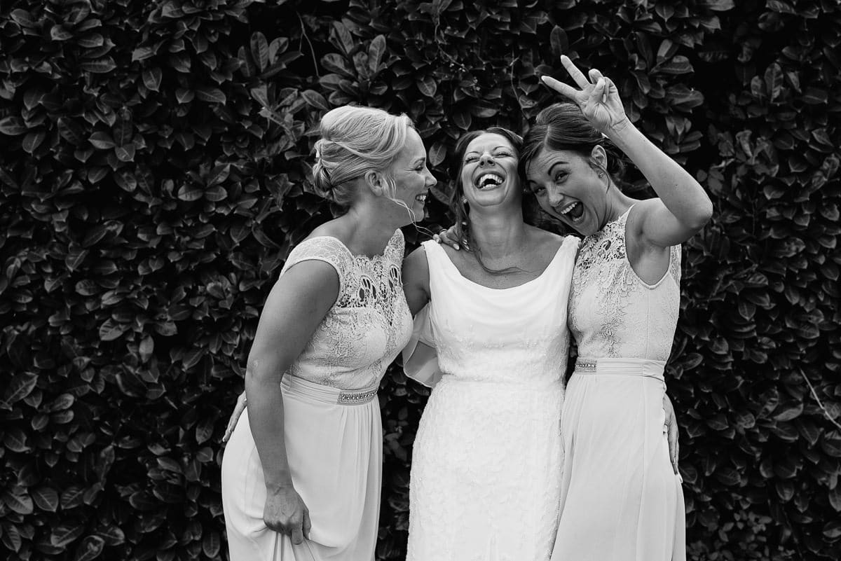 bride in wedding dress with bridesmaids having a laugh