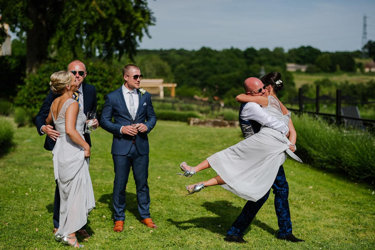 bridesmaid being swept off her feet on lawn at wedding