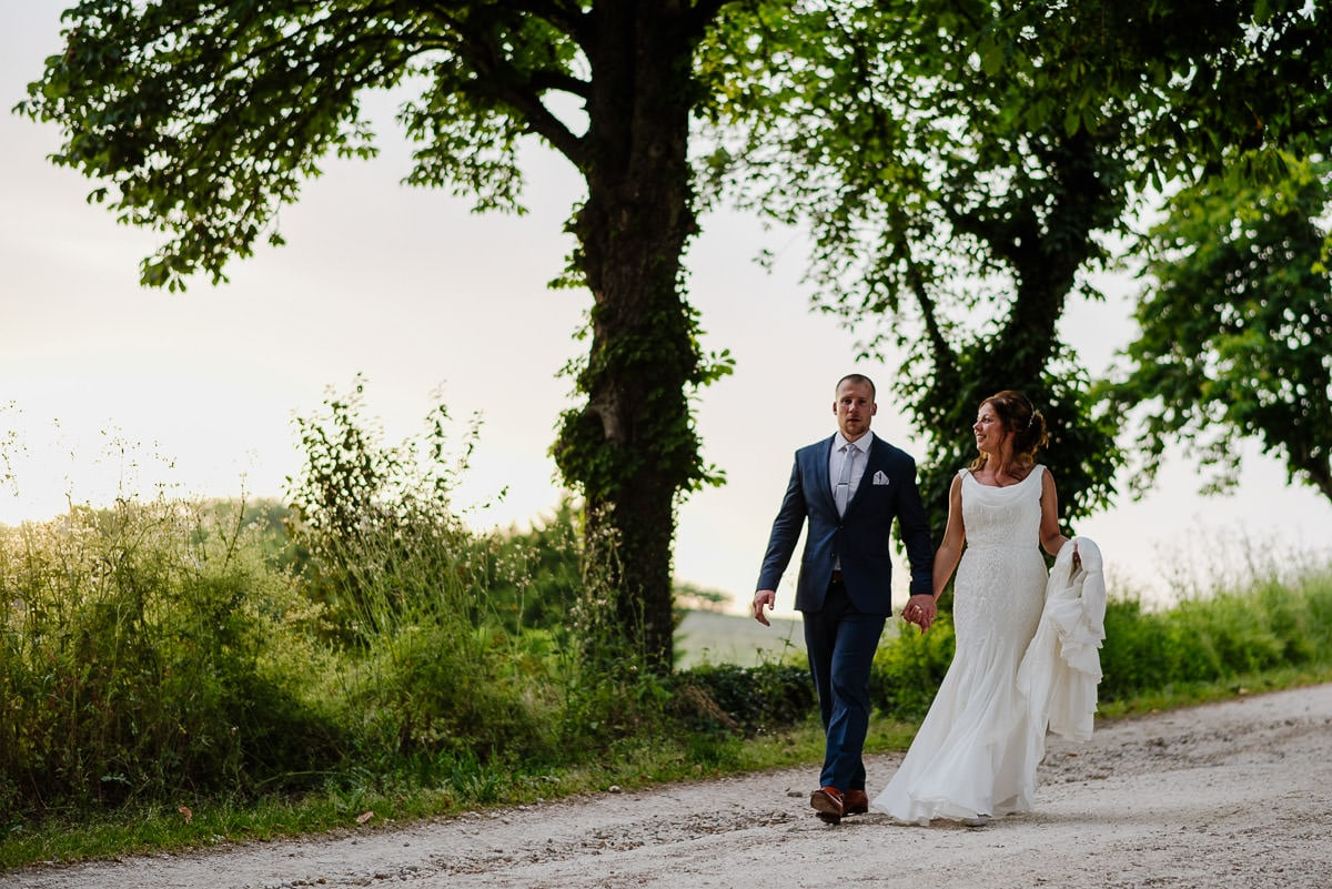 Bride and groom walking down driveway at french Chateau