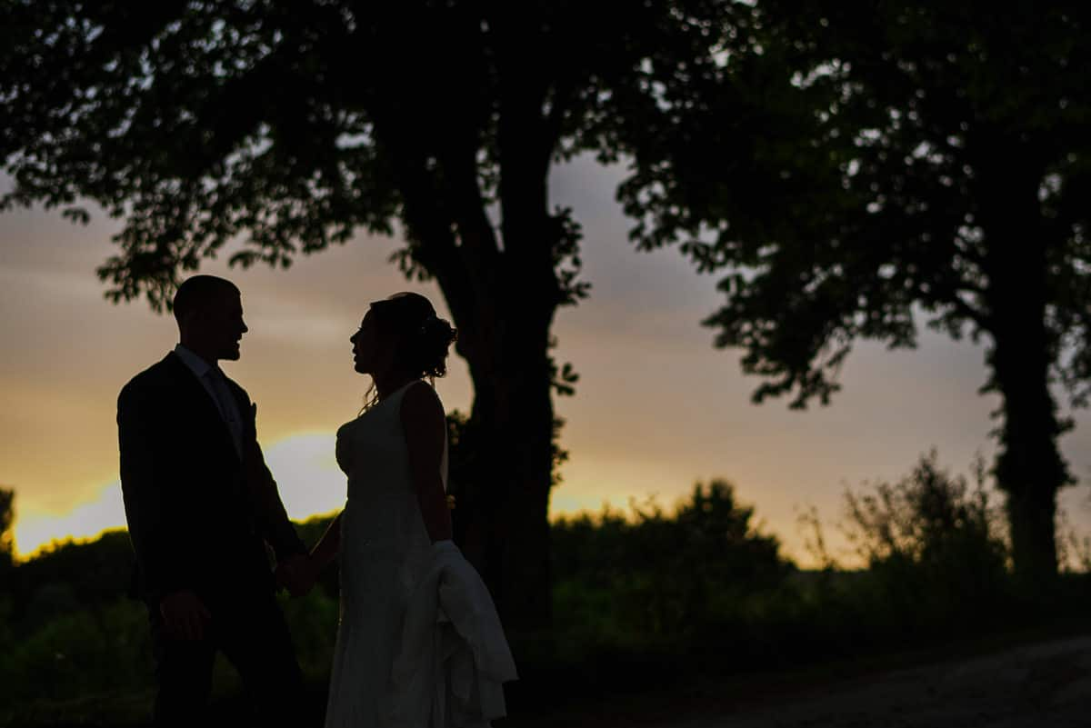 Bride and groom silhouetted at sunset in france