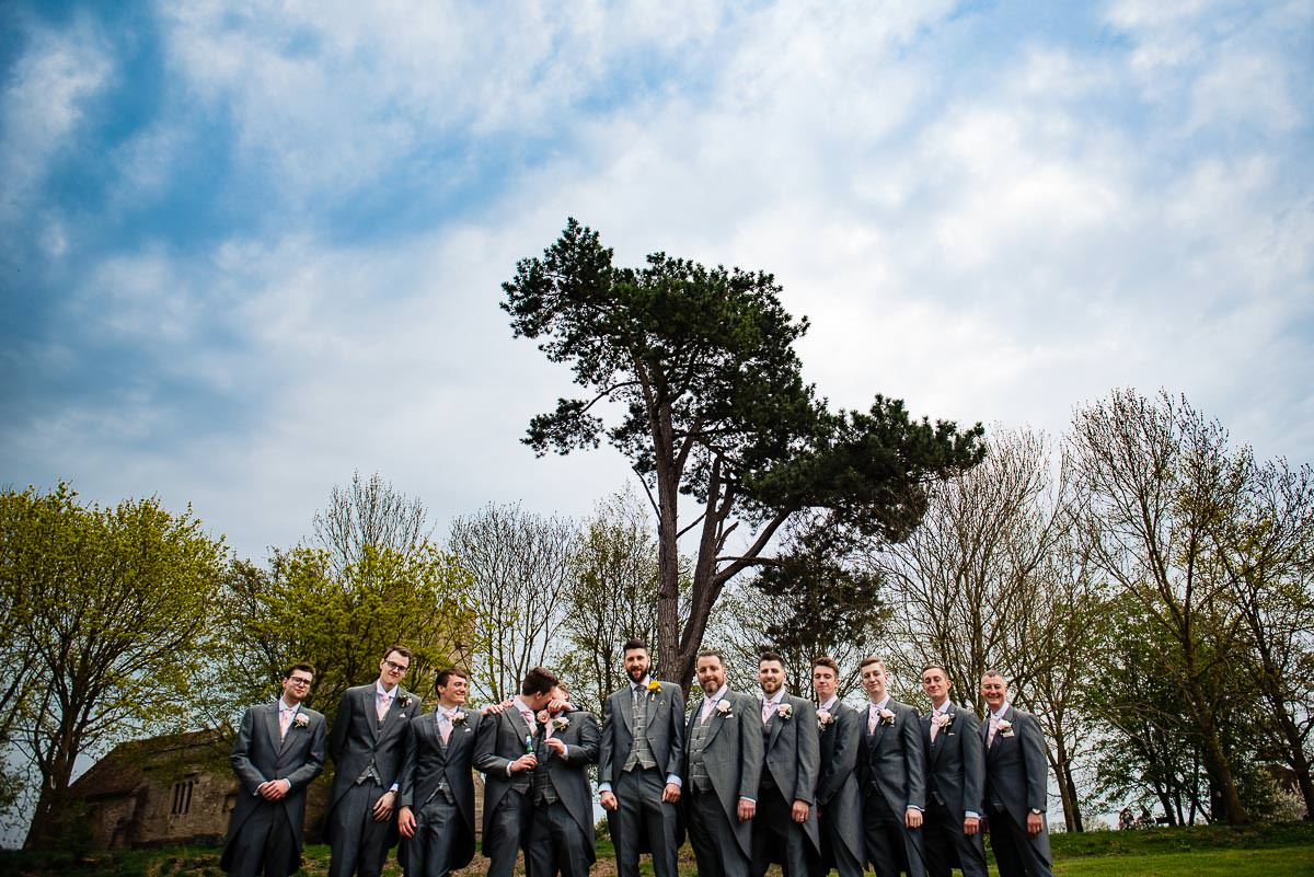 groom and groomsmen in morning suits gather outside for a photo