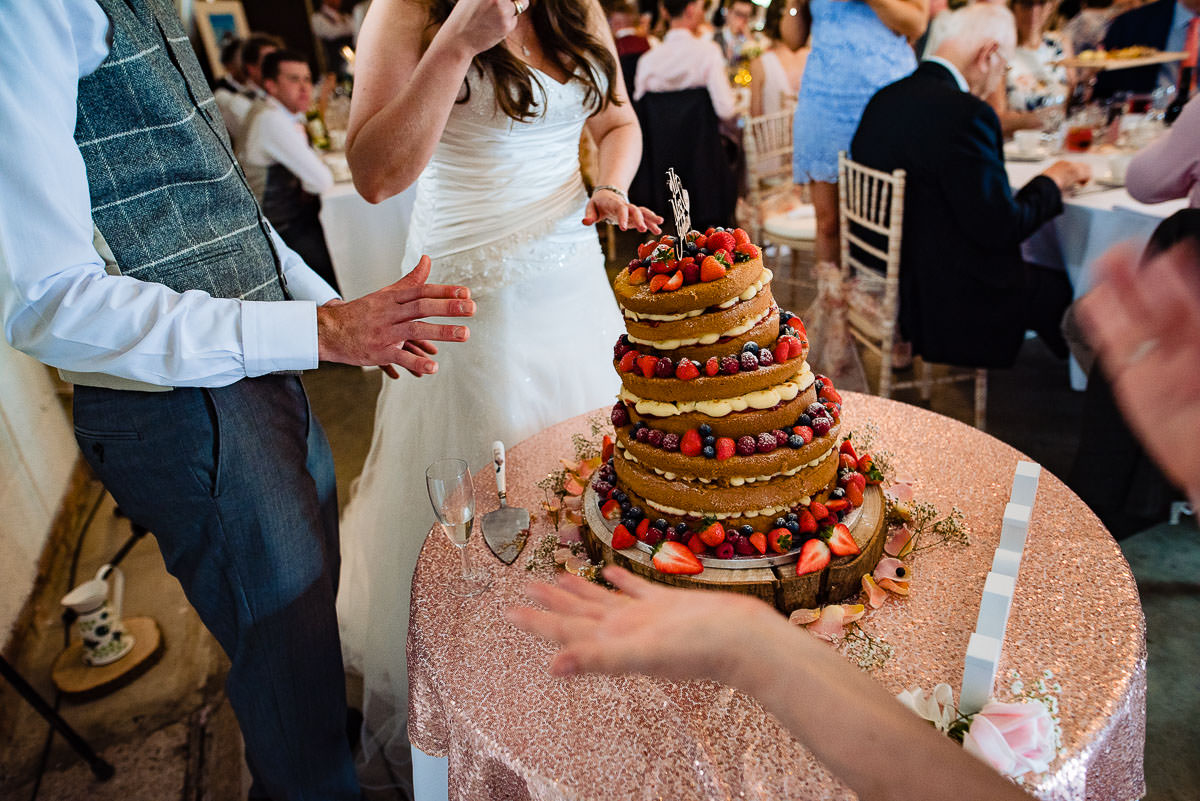 toppling naked strawberry wedding cake