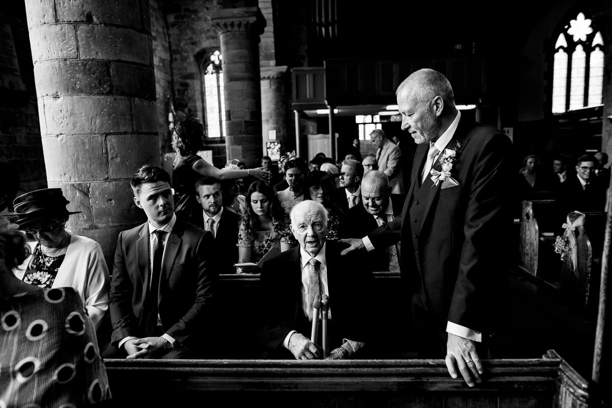 elderly wedding guest seated on pew as the ceremony begins