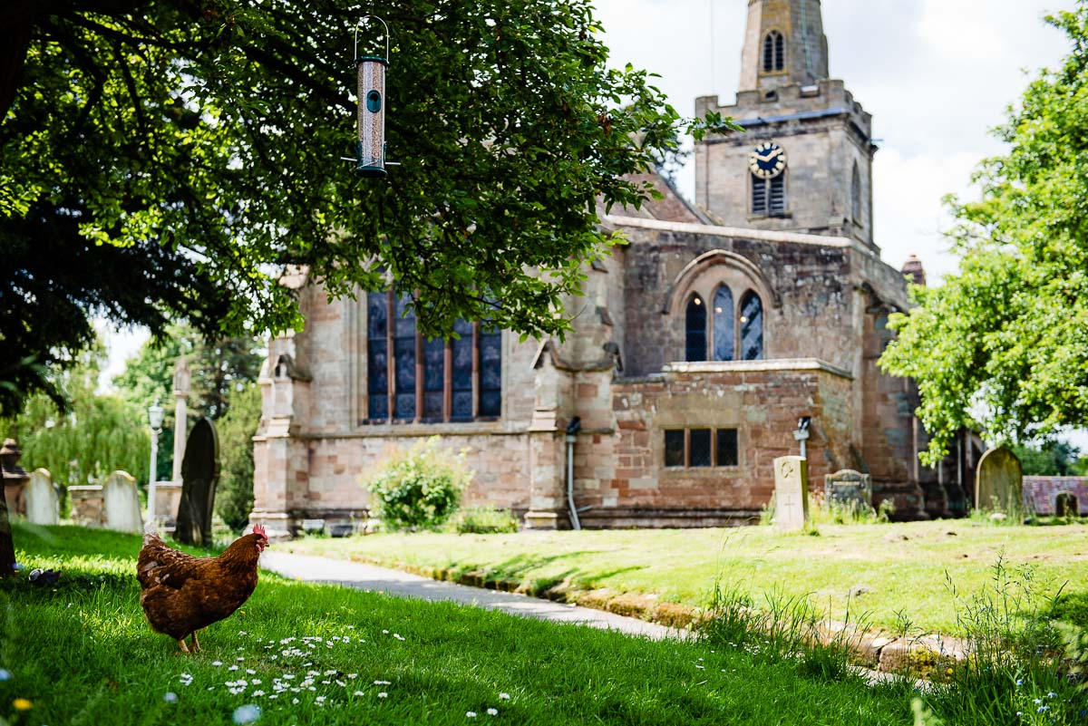 Church exterior with chicken enjoying the sun in grounds