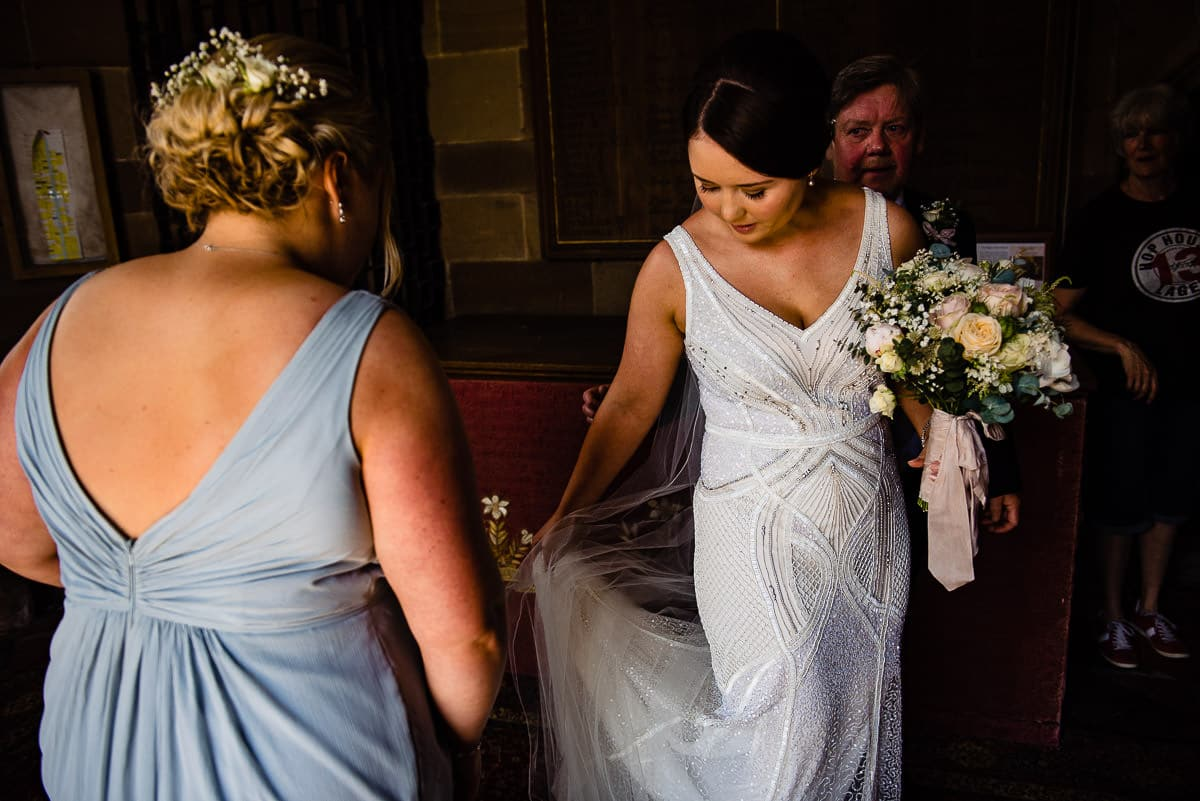 bride and bridesmaid adjust the dress before walking down the aisle