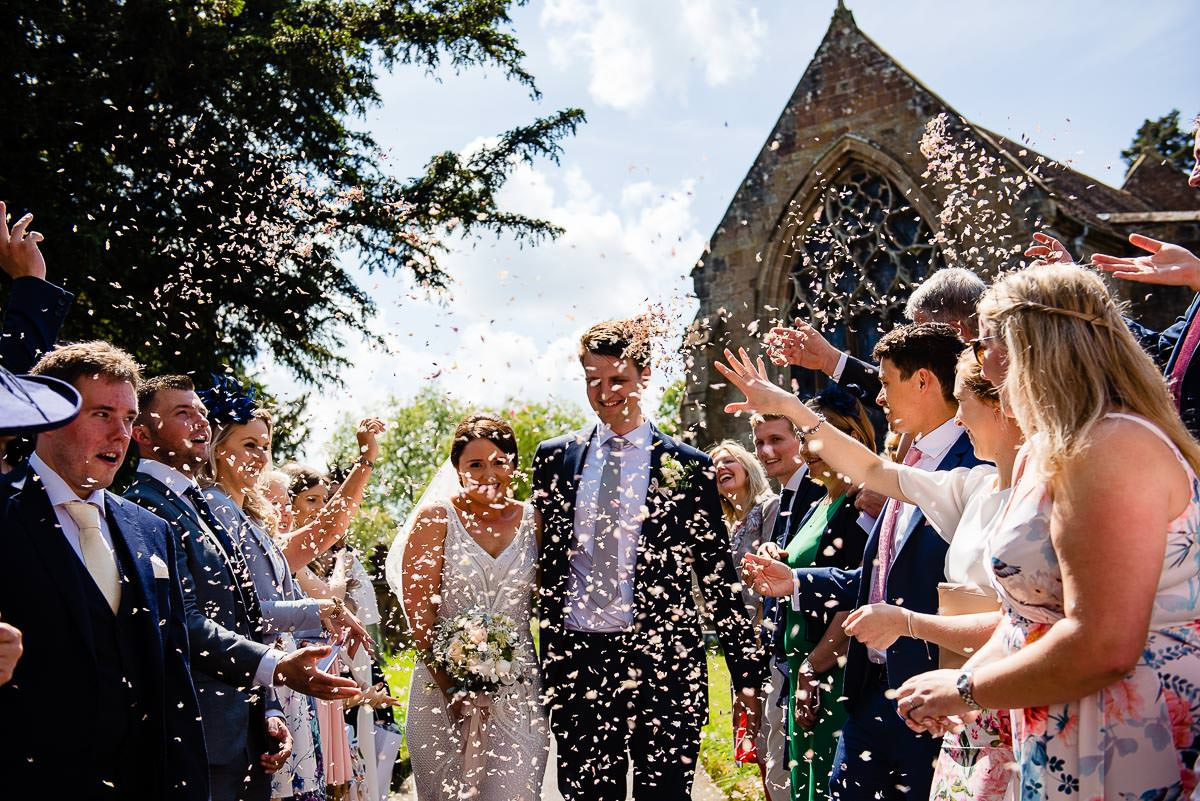 wedding guests throw confetti the newly wedded couple outside church