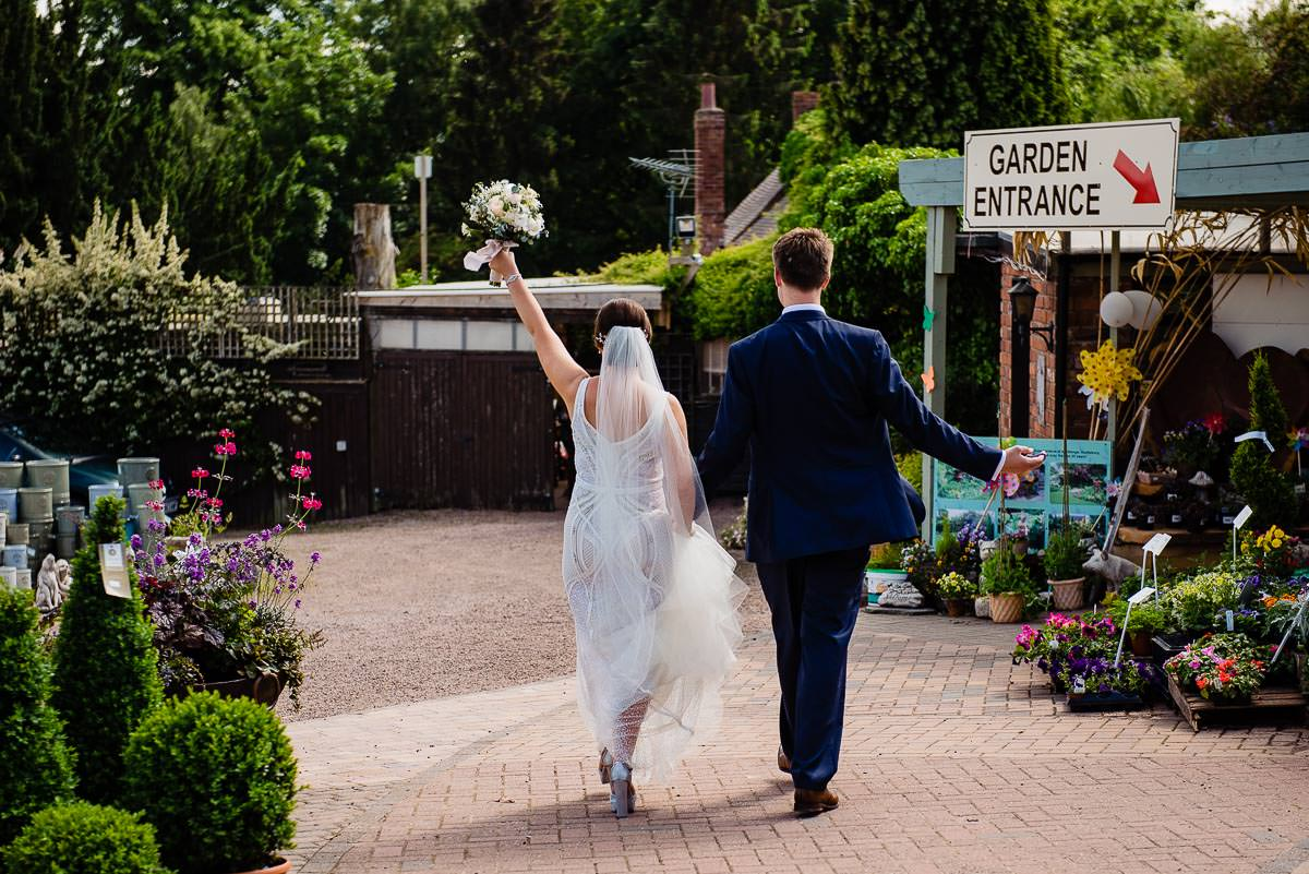 bride and groom walk hand in hand with bouquet in the air