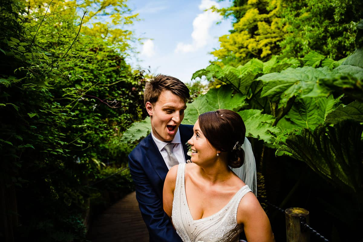 bride and groom have fun between bright green garden foliage