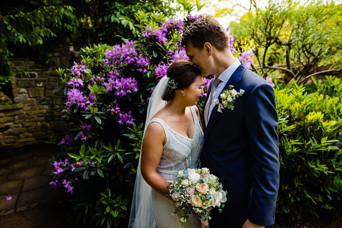 bride and groom with colourful flowers at their country garden wedding