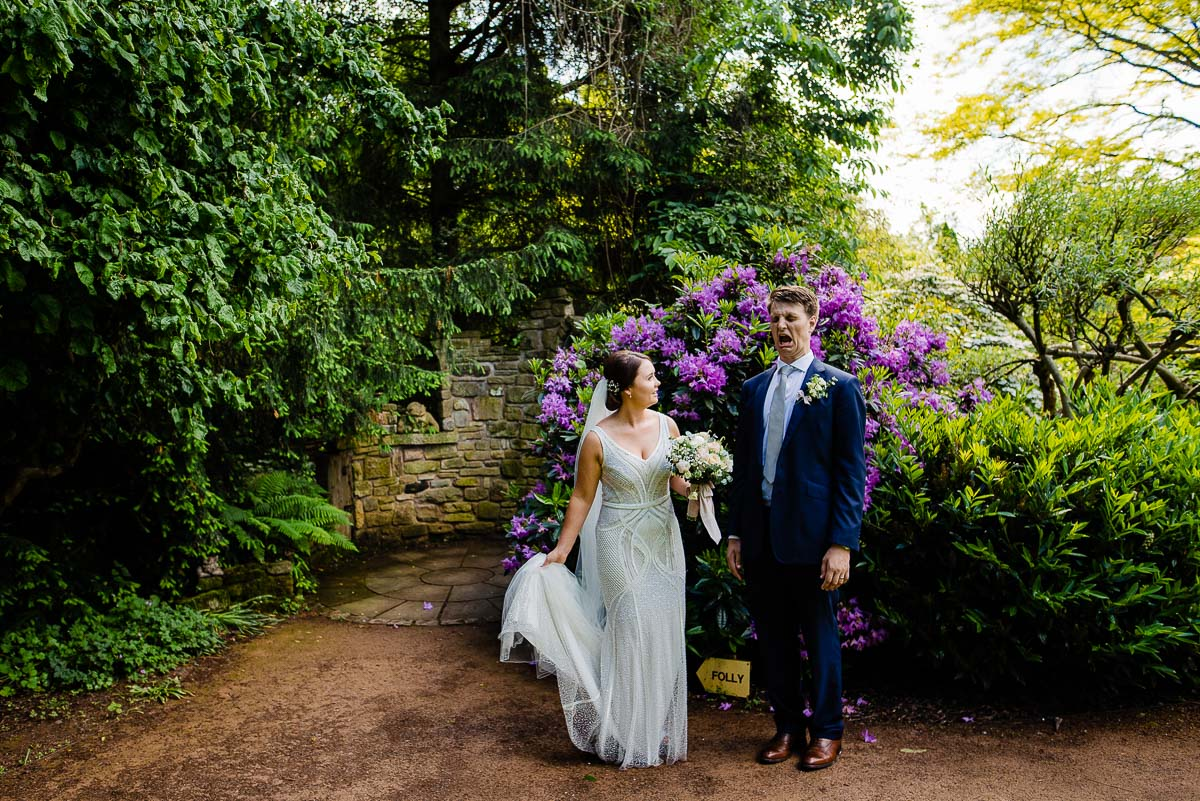 groom pulls funny face during portraits in the garden