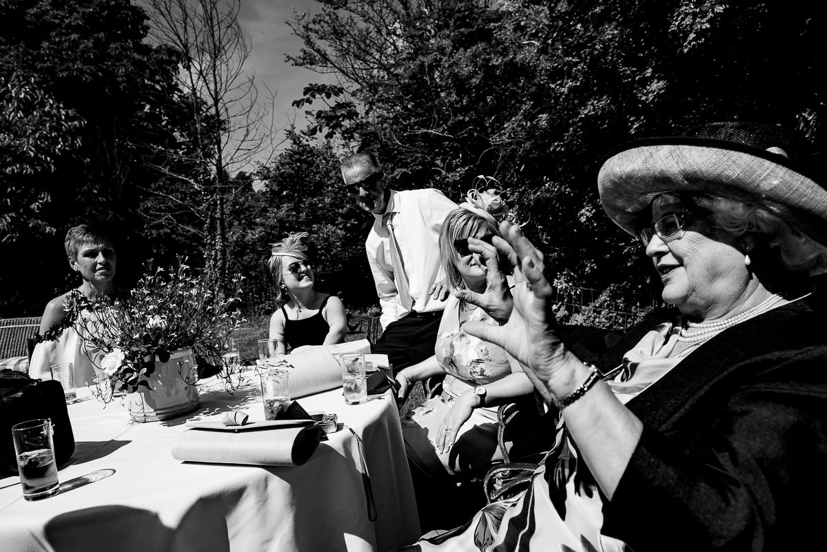 wedding guests mingle and tell stories at garden table