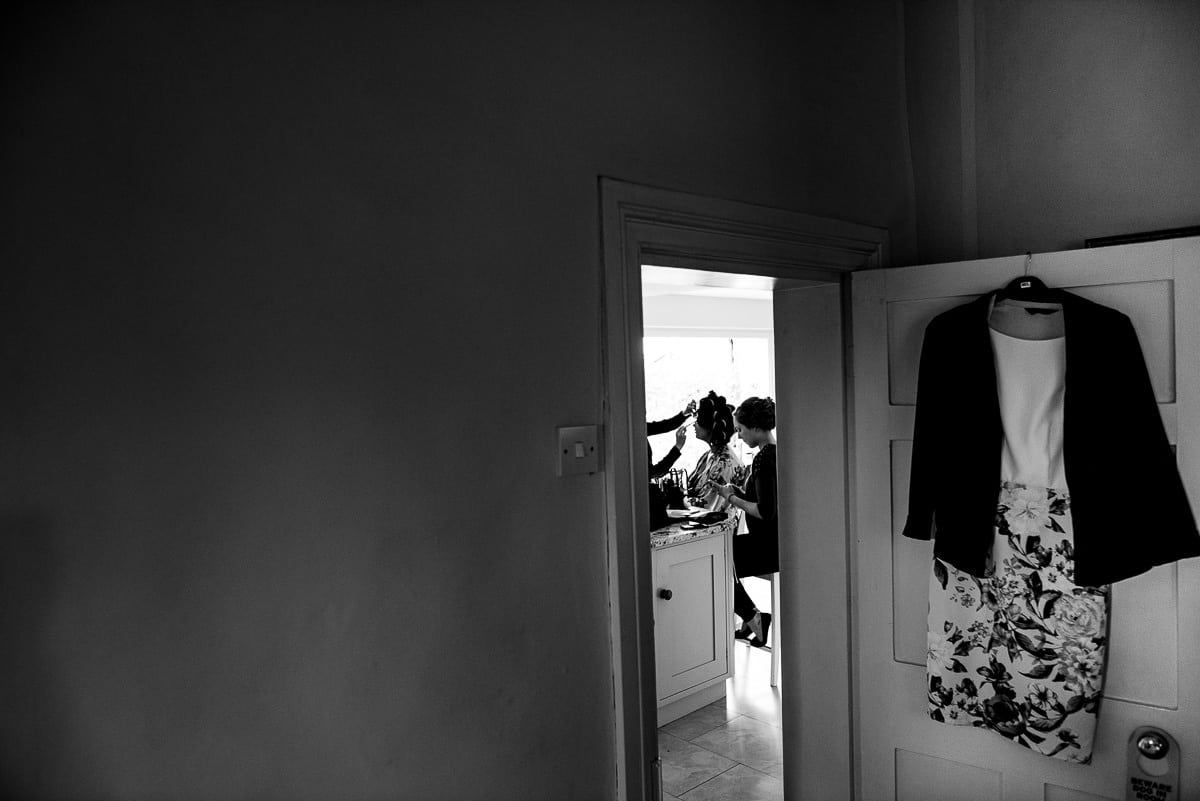 black and white image of bridesmaids getting ready framed in doorway