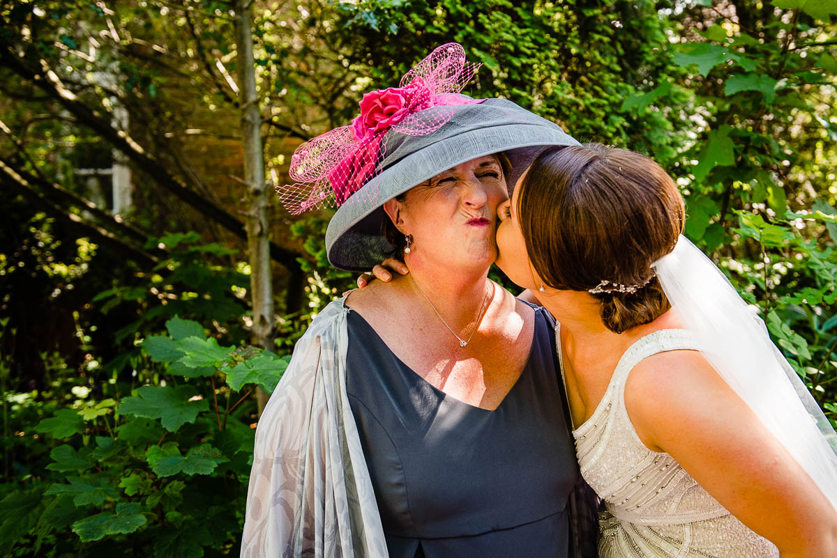 bride kisses her mother on the cheek