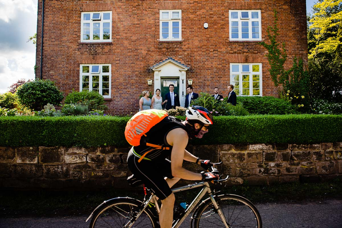 cyclist speeds past wedding party as they gather outside red bricked country house