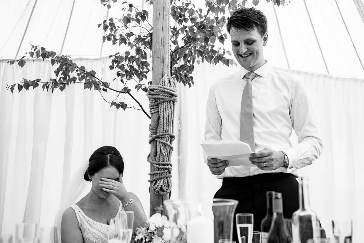 bride blushes as groom reads embarrassing speech in marquee
