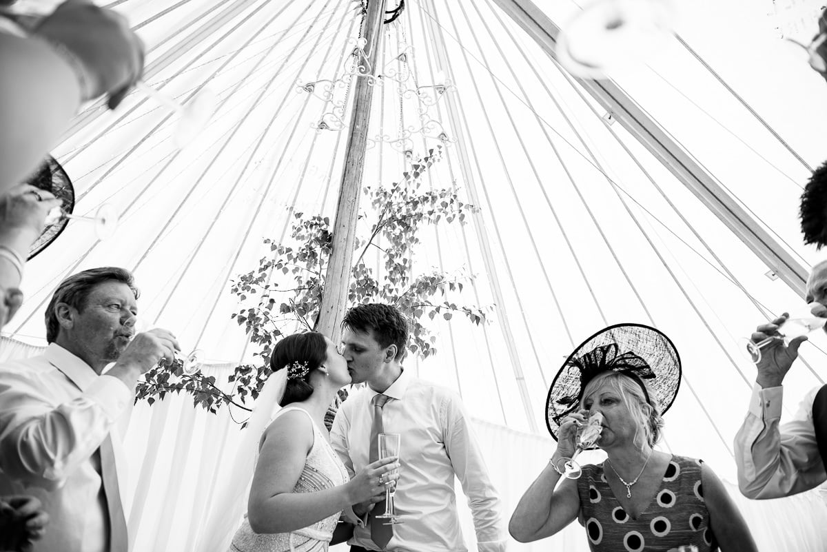bride and groom kiss inside their garden marquee wedding venue