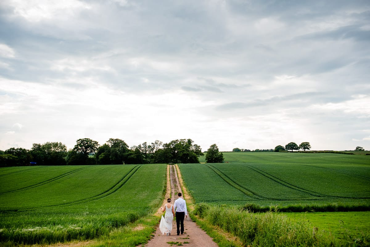bride and groom walk hand in hand into the distance of a countryside field