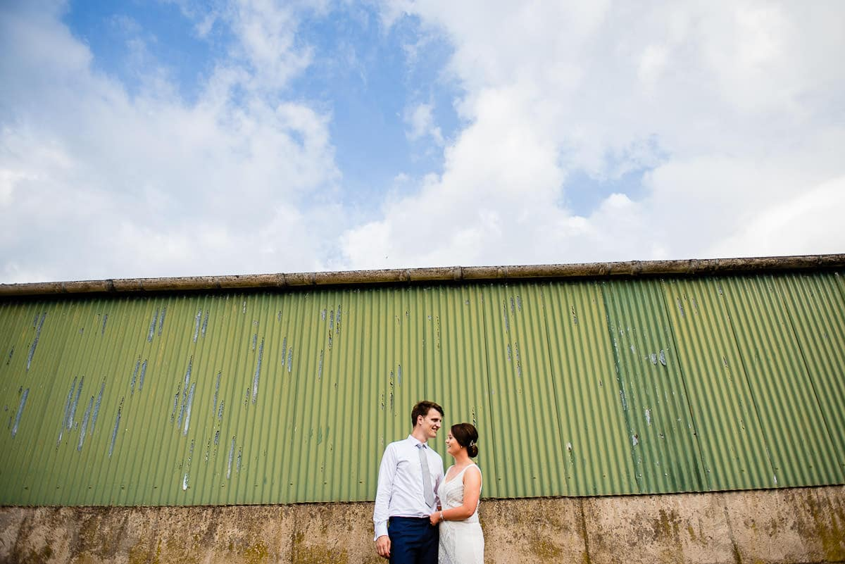bride and groom stand in front of rustic old green metal barn
