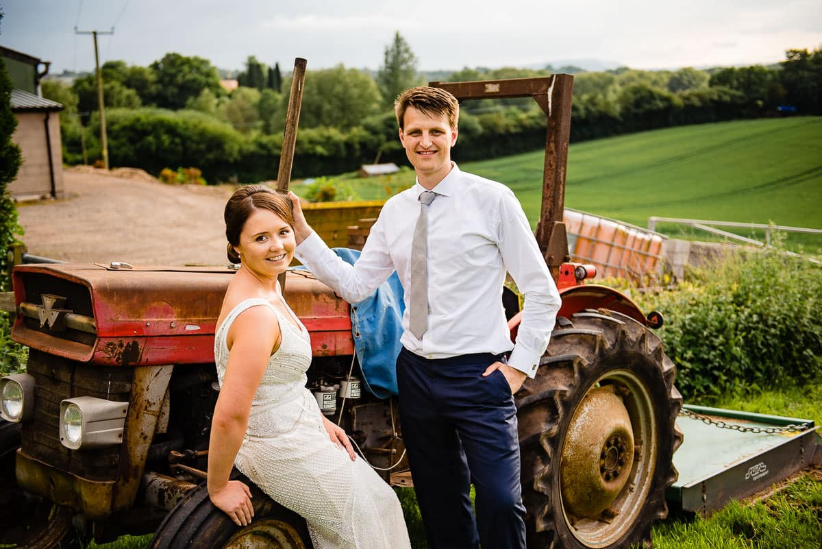 bride and groom pose on tractor in the countryside