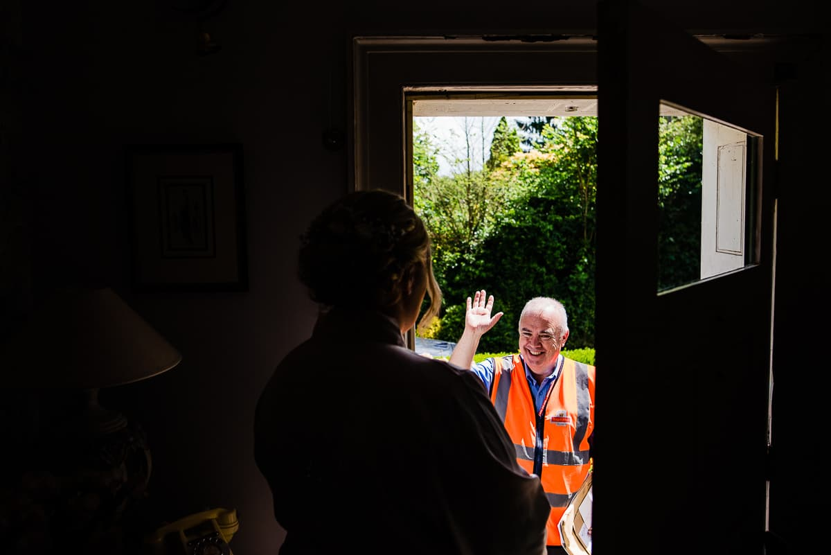 postman delivers mail to the brides house