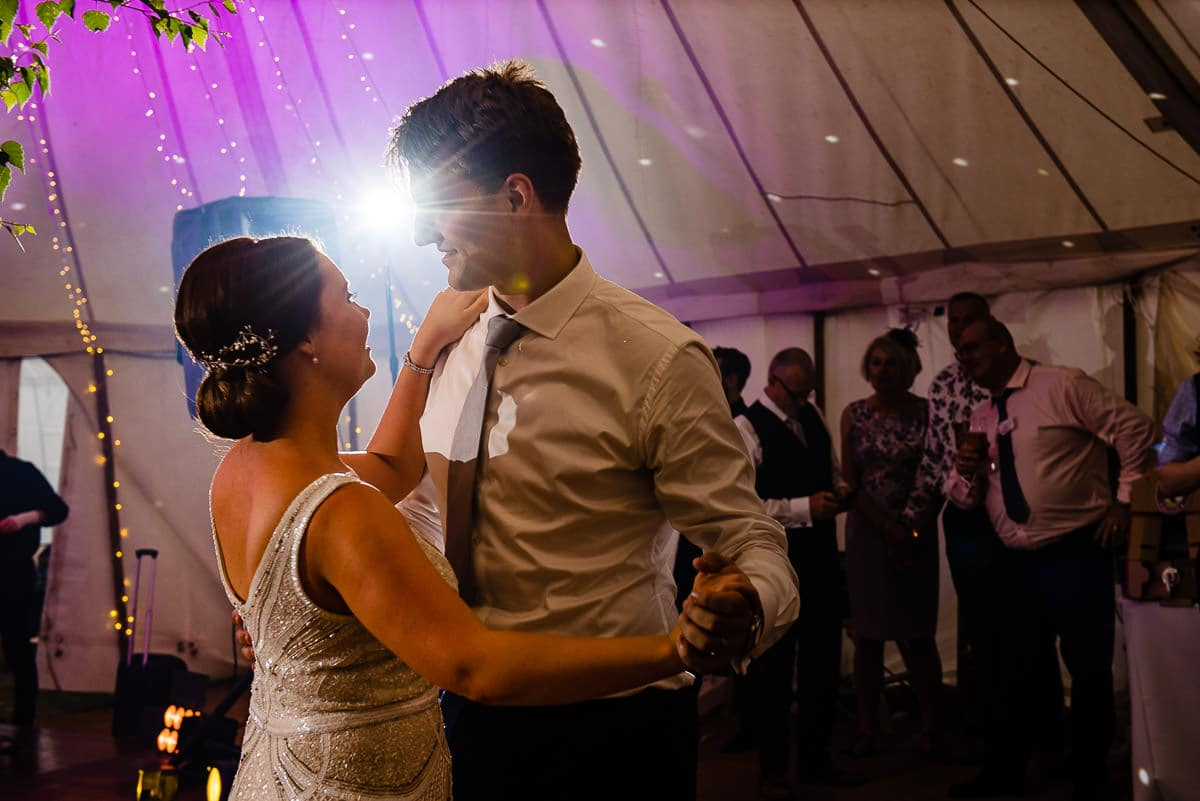 bride and groom share first dance in marquee as guests spectate