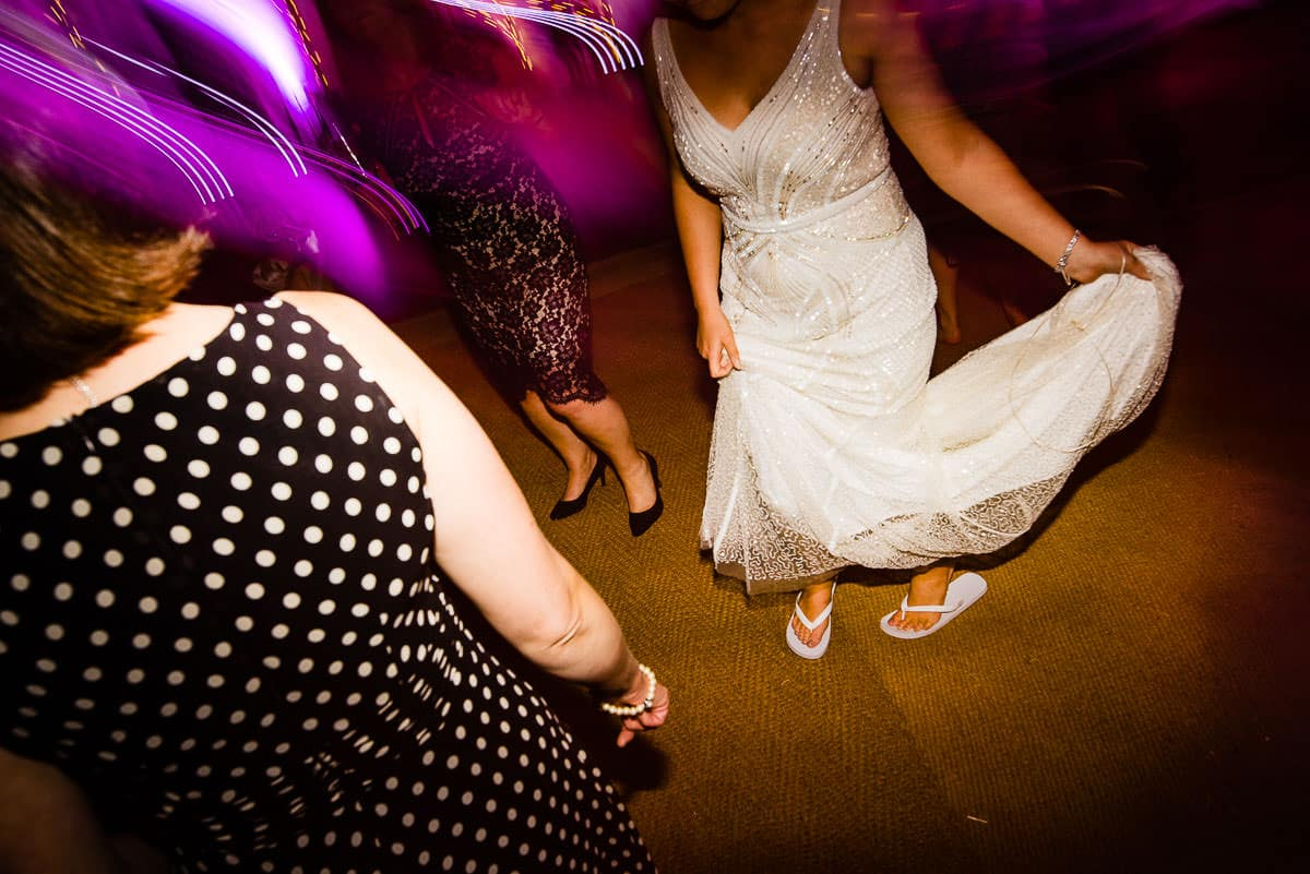 bride wears flat sandals on wedding dance floor