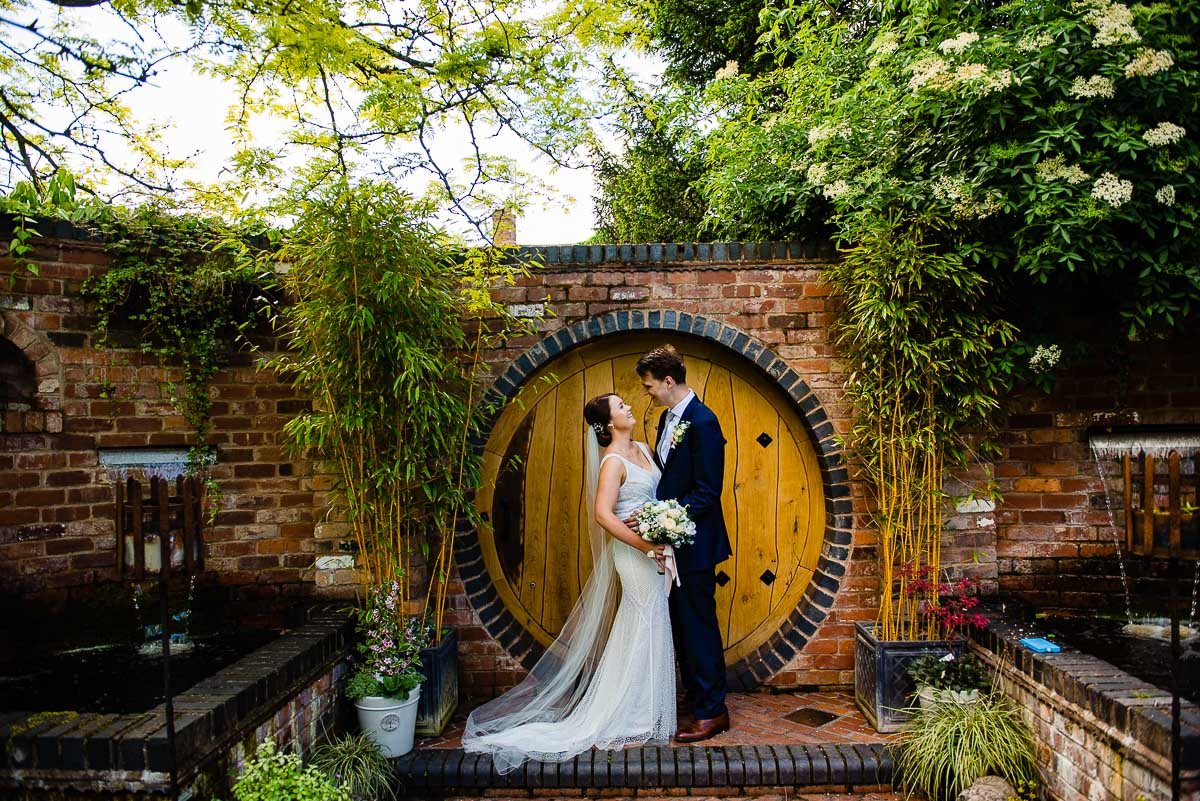 bride and groom pose in front of rustic garden wall with hobbit door