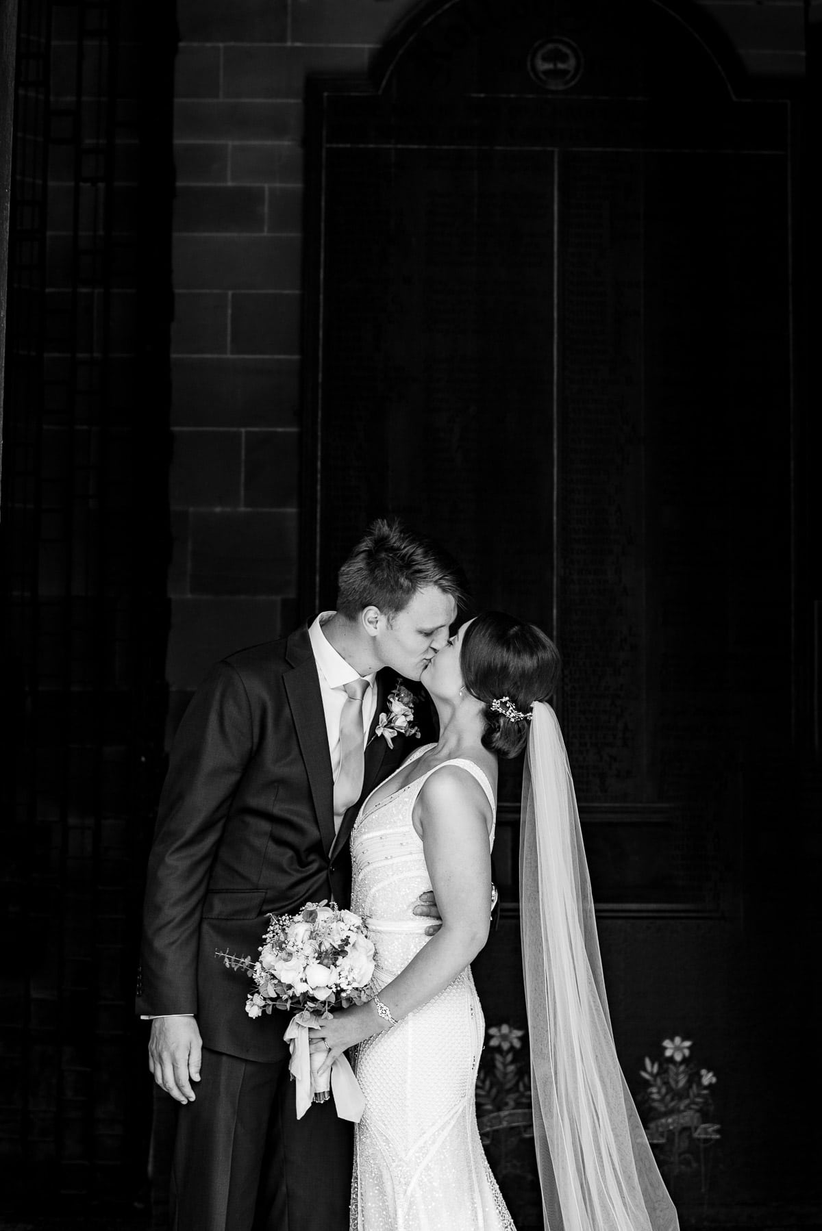 bride with long veil kisses tall groom outside church