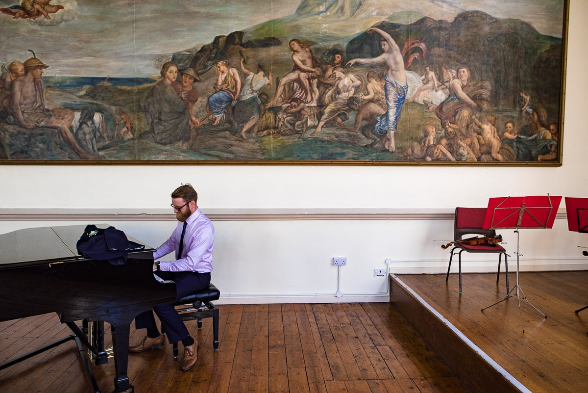 Wedding guests plays piano in front of antique painting in Malvern Collage