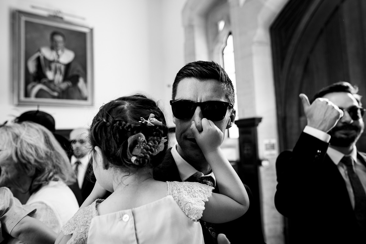 candid portrait of little girl pinching wedding guests nose